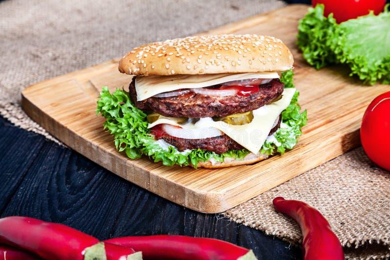 Διπλό Burger με το κρέας, τη σάλτσα και τα λαχανικά επάνω στο ξύλινο υπόβαθρο στοκ εικόνα