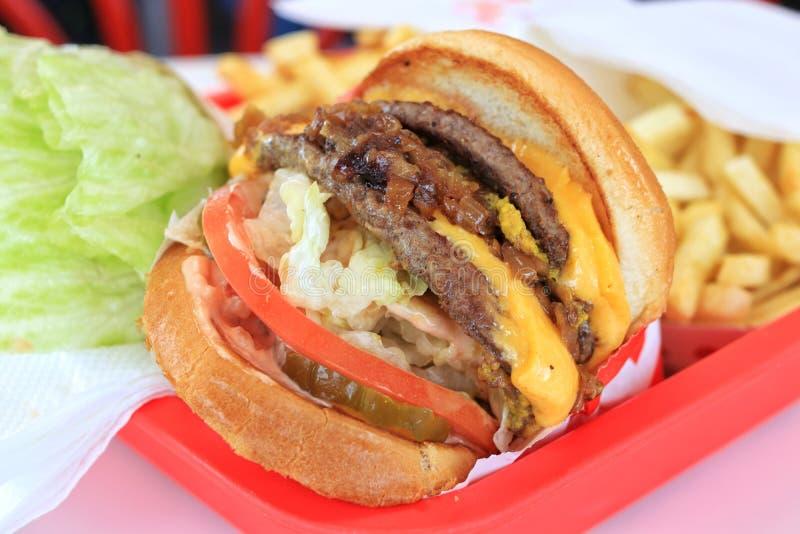 Διπλό cheeseburger, με τις τηγανιτές πατάτες στοκ εικόνες