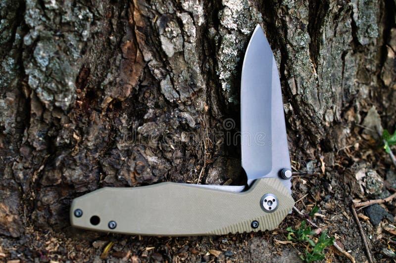 Διπλώνοντας τον τουρίστα, το μαχαίρι στρατοπέδευσης με τη μαύρη λεπίδα και μια λαβή τρελλή στοκ φωτογραφία