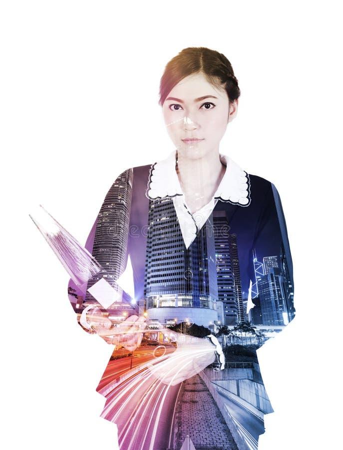 Διπλή έκθεση της επιχειρησιακής γυναίκας με τους φακέλλους ενάντια στην πόλη στοκ εικόνες