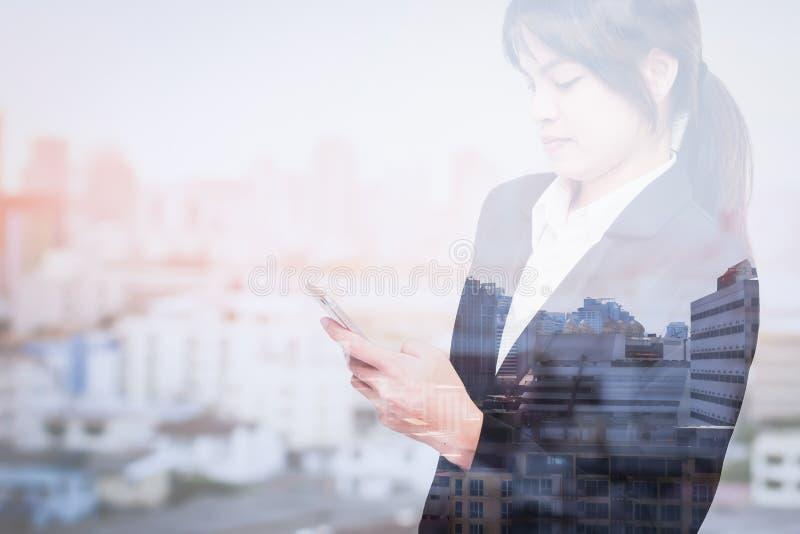 Διπλή έκθεση της επιχειρησιακής γυναίκας που χρησιμοποιεί το έξυπνο τηλέφωνο με την πόλη θαμπάδων στοκ φωτογραφίες