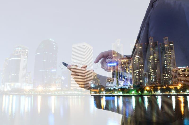 Διπλή έκθεση του ατόμου πόλεων και επιχειρήσεων που χρησιμοποιεί το ψηφιακό smartphon στοκ φωτογραφία