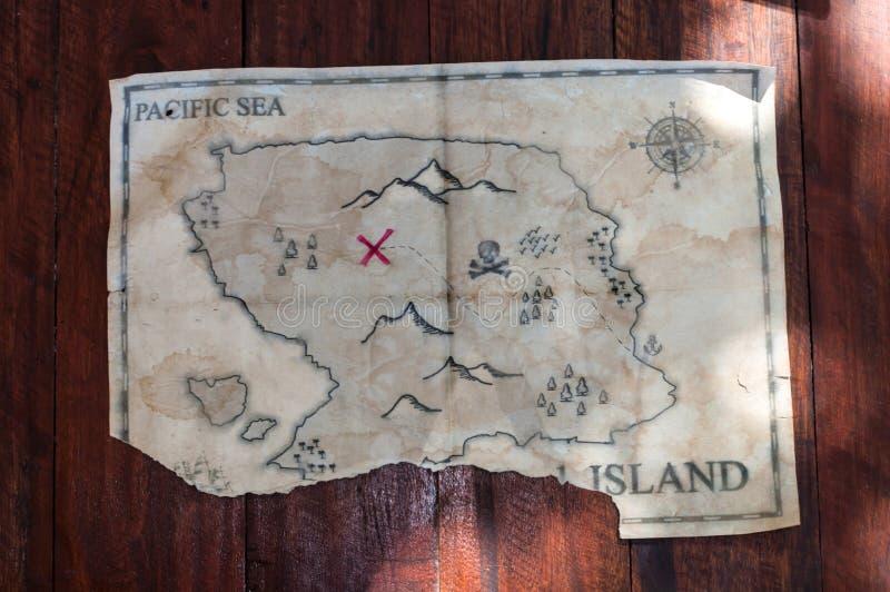 Διπλωμένος εκλεκτής ποιότητας πλαστός χάρτης του αφηρημένου νησιού και Ερυθρός Σταυρός του στήθους θησαυρών στον ξύλινο πίνακα στοκ φωτογραφία με δικαίωμα ελεύθερης χρήσης