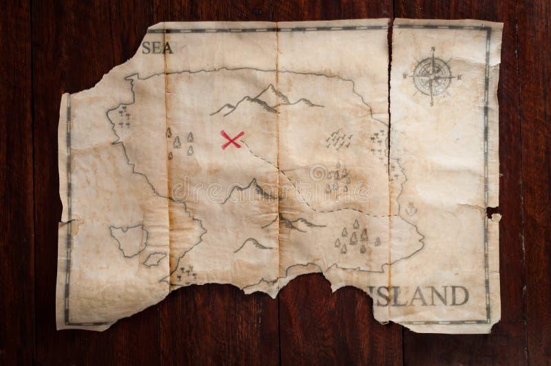 Διπλωμένος εκλεκτής ποιότητας χάρτης θησαυρών με τον Ερυθρό Σταυρό του στήθους πειρατών στο ξύλινο επιτραπέζιο υπόβαθρο στοκ φωτογραφία με δικαίωμα ελεύθερης χρήσης