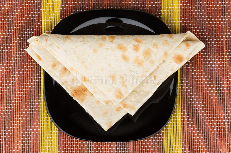 Διπλωμένο τρίγωνο του λεπτού αρμενικού lavash στο μαύρο πιάτο στο χαλί στοκ εικόνα με δικαίωμα ελεύθερης χρήσης