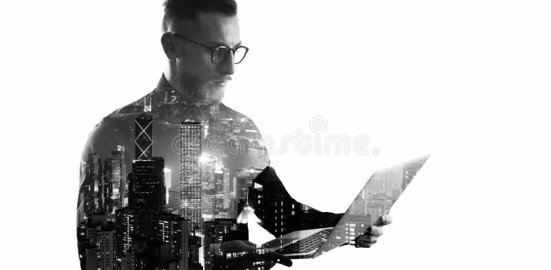 Διπλός γενειοφόρος επιχειρηματίας έκθεσης που φορά το μαύρα πουκάμισο και τα γυαλιά Τραπεζίτης που κρατά τα σύγχρονα χέρια σημειω στοκ φωτογραφία