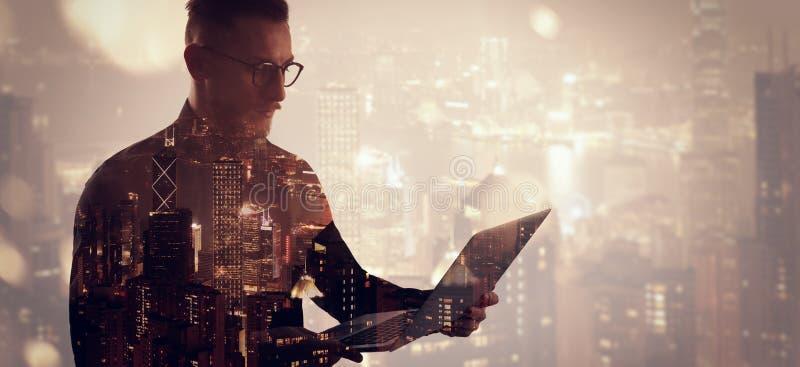 Διπλός γενειοφόρος επιχειρηματίας έκθεσης που φορά το μαύρα πουκάμισο και τα γυαλιά Τραπεζίτης που κρατά τα σύγχρονα χέρια σημειω στοκ εικόνα με δικαίωμα ελεύθερης χρήσης