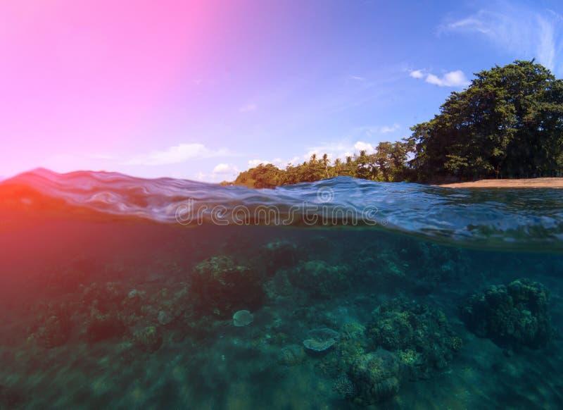 Διπλό τοπίο με τη θάλασσα και τον ουρανό Υποθαλάσσια άποψη της κοραλλιογενούς υφάλου Τροπική ακτή νησιών στοκ φωτογραφία