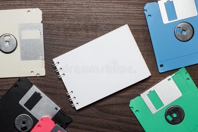 Δισκέτες και κενό σημειωματάριο στο ξύλινο υπόβαθρο στοκ εικόνες