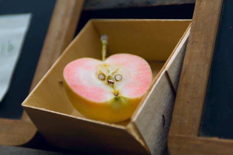 Διχοτομημένο ellow μήλο σε ένα ξύλινο κιβώτιο στοκ φωτογραφίες