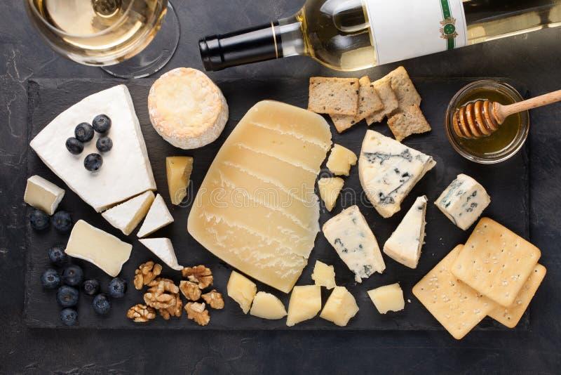 Δοκιμάζοντας πιάτο τυριών σε ένα σκοτεινό πιάτο πετρών Τρόφιμα για το κρασί και ρομαντική ημερομηνία, λιχουδιές τυριών σε ένα μαύ στοκ φωτογραφίες