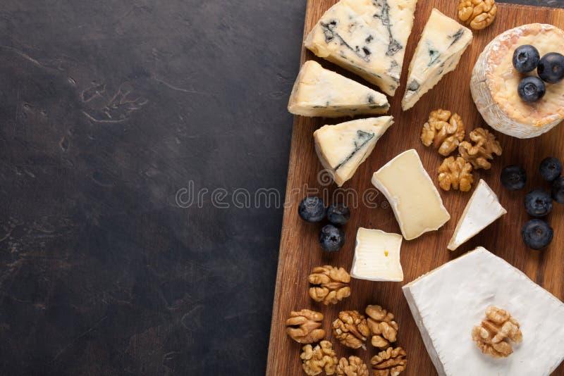 Δοκιμάζοντας πιάτο τυριών σε ένα σκοτεινό πιάτο πετρών Τρόφιμα για το κρασί και ρομαντική ημερομηνία, λιχουδιές τυριών σε ένα μαύ στοκ φωτογραφία με δικαίωμα ελεύθερης χρήσης