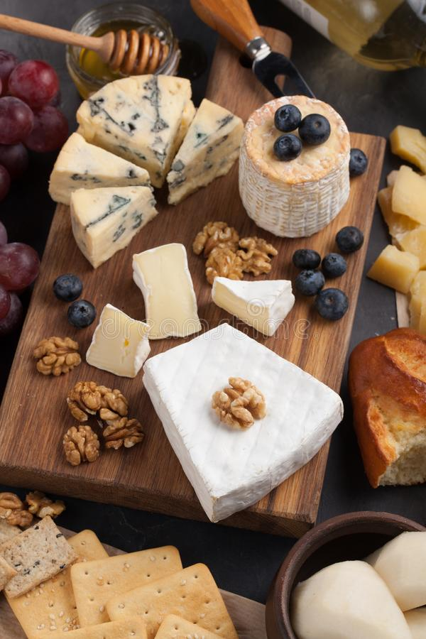 Δοκιμάζοντας πιάτο τυριών σε ένα σκοτεινό πιάτο πετρών Τρόφιμα για το κρασί και ρομαντική ημερομηνία, λιχουδιές τυριών σε ένα μαύ στοκ εικόνα με δικαίωμα ελεύθερης χρήσης