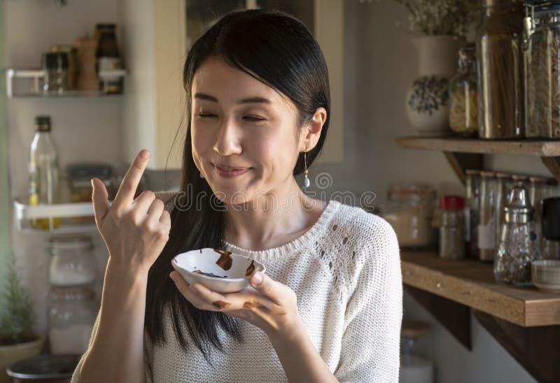 Δοκιμάζοντας σάλτσα σοκολάτας γυναικών από ένα φλυτζάνι στοκ φωτογραφία