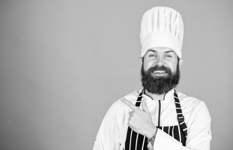 Δοκιμάστε κάτι ειδικό Βέβαιος γενειοφόρος ευτυχής άσπρος ομοιόμορφος αρχιμαγείρων Το μυστικό μου τοποθετεί αιχμή σε μαγειρικό Μαγ στοκ φωτογραφίες