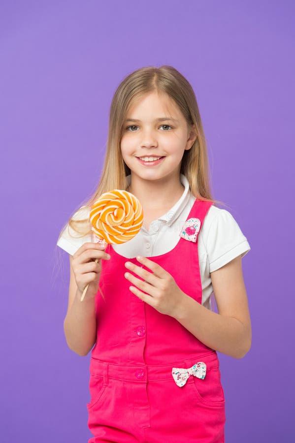 Δοκιμάστε το μικρό παιδί lollipop μου που χαμογελά με το ραβδί καραμελών στο πορφυρό υπόβαθρο Χαμόγελο κοριτσιών με το lollipop σ στοκ εικόνα