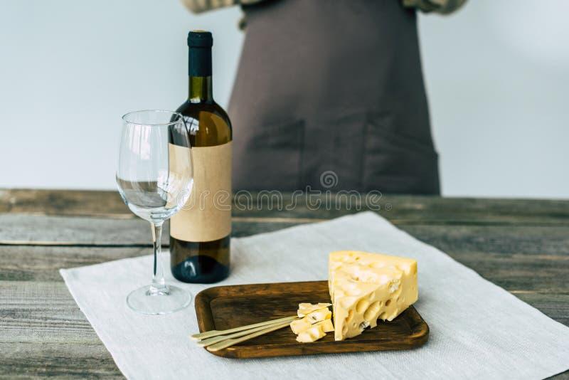 Δοκιμαστής που στέκεται στον πίνακα με το μπουκάλι του άσπρου κρασιού, κενό γυαλί στοκ εικόνες