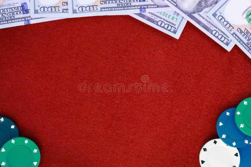 Δολάρια και τσιπ πόκερ στο κόκκινο αισθητό χαρτοπαικτική λέσχη επιτραπέζιο υπόβαθρο στοκ φωτογραφίες