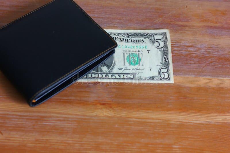 δολάρια με το μαύρο πορτοφόλι δέρματος στο ξύλινο πάτωμα στοκ εικόνες