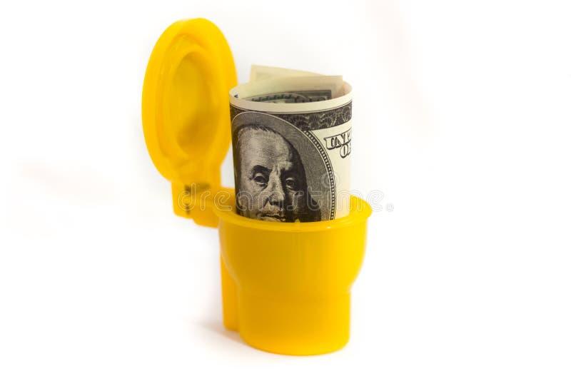 Δολάρια στην τουαλέτα σε ένα άσπρο υπόβαθρο στοκ εικόνες