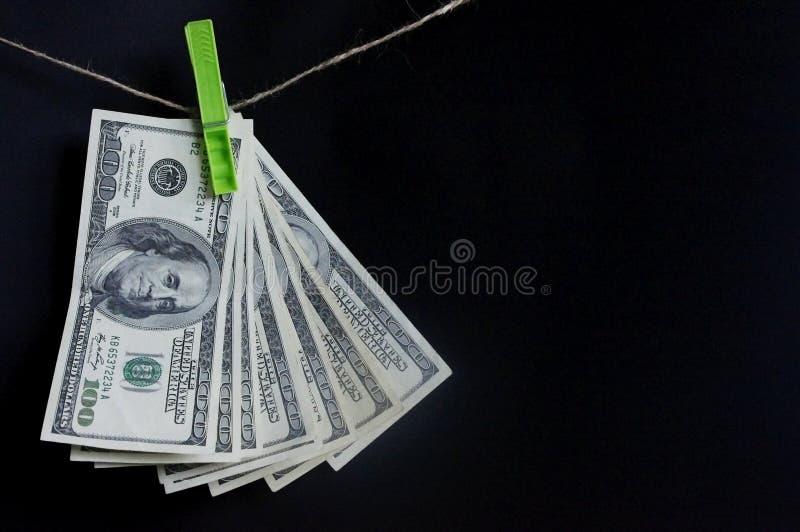 Δολάρια στο σχοινί με τα clothespins Ανεμιστήρας των χρημάτων σε ένα σκοτεινό υπόβαθρο στοκ εικόνες