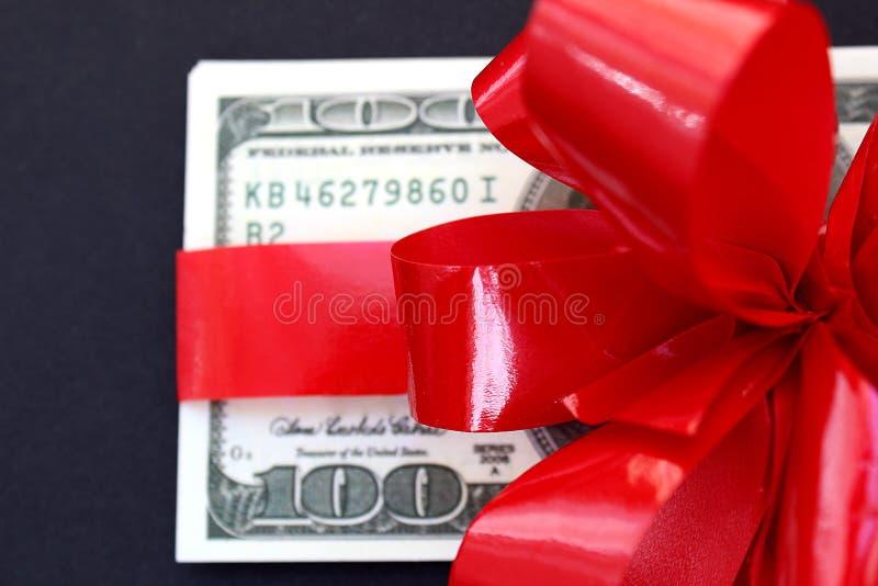 Δολάρια χρημάτων που τυλίγονται σε ένα τόξο σε ένα δώρο στοκ φωτογραφία με δικαίωμα ελεύθερης χρήσης