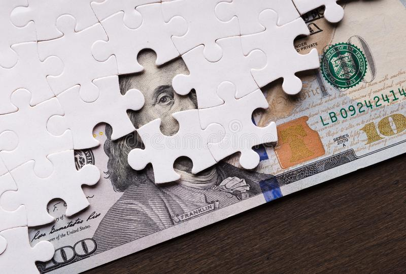 Δολάριο που κρύβεται αμερικανικό κάτω από τα κομμάτια γρίφων στοκ φωτογραφία