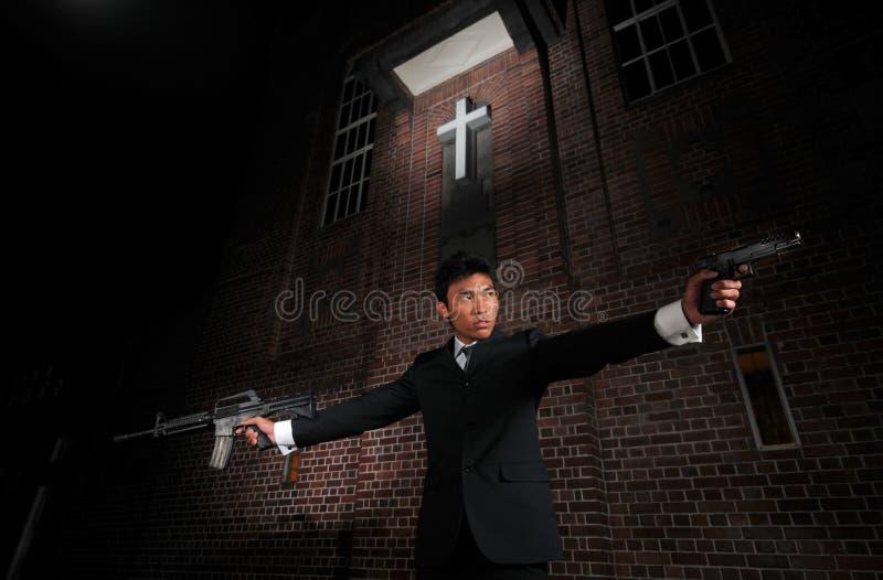 δολοφόνος πυροβόλων όπλων πρακτόρων που δείχνει το στόχο προς στοκ εικόνα
