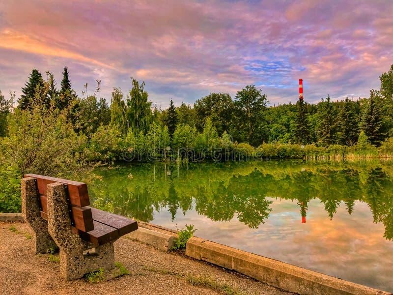 Δονούμενη ανατολή πέρα από μια ήρεμη λίμνη πάρκων στοκ εικόνα