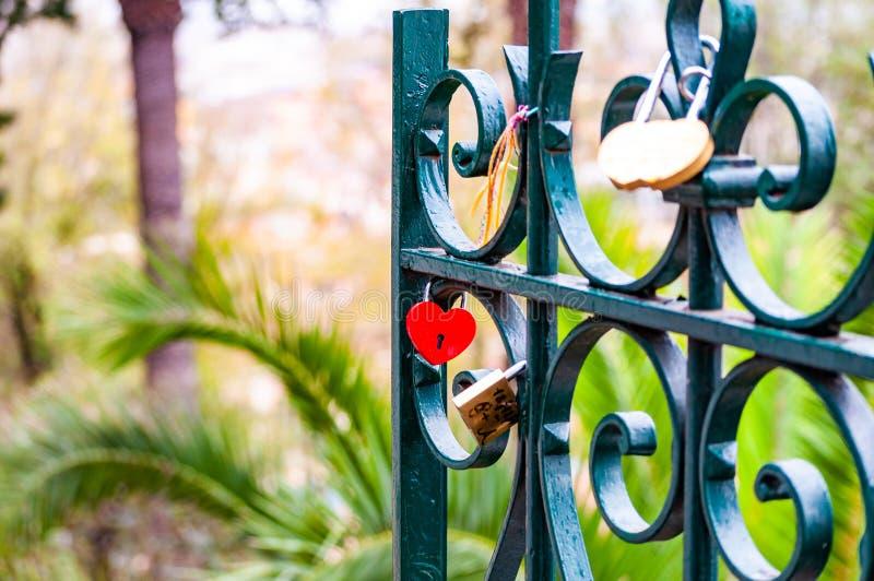 Δονούμενη κόκκινη ένωση κλειδαριών μετάλλων μορφής καρδιών στον πράσινο φράκτη μετάλλων στοκ εικόνα με δικαίωμα ελεύθερης χρήσης