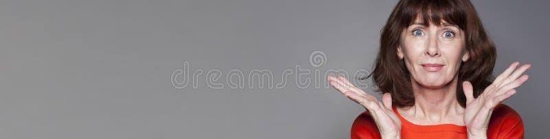 Δονούμενη μέση ηλικίας γυναίκα που εκφράζει την απόγνωση και την επίπληξη, γκρίζο έμβλημα στοκ φωτογραφίες με δικαίωμα ελεύθερης χρήσης
