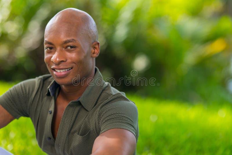 Δονούμενο πορτρέτο ένα όμορφο νέο άτομο αφροαμερικάνων που χαμογελά στη κάμερα Το άτομο θέτει υπαίθρια σε ένα πάρκο τη ρύθμιση στοκ εικόνες