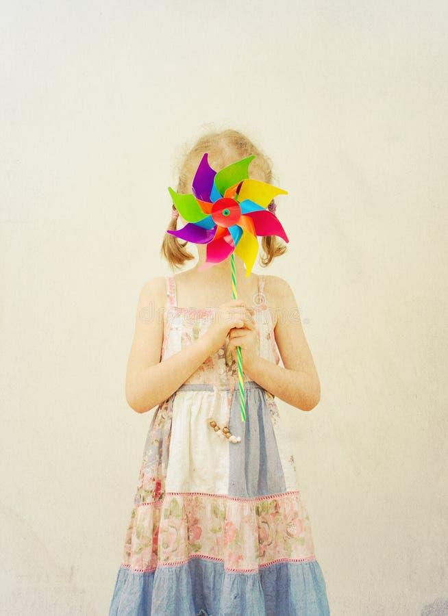 Δορές μικρών κοριτσιών πίσω από το ζωηρόχρωμο pinwheel στοκ εικόνες με δικαίωμα ελεύθερης χρήσης