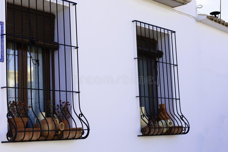 Δοχεία αργίλου στο παράθυρο πίσω από ένα σφυρηλατημένο πλέγμα σε έναν άσπρο τοίχο στην παλαιά πόλη Altea, Ισπανία στοκ φωτογραφία