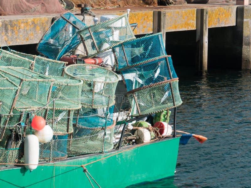 Δοχεία αστακών που συσσωρεύονται σε ένα αλιευτικό σκάφος σε ένα λιμάνι αλιείας στην Πορτογαλία στοκ φωτογραφία