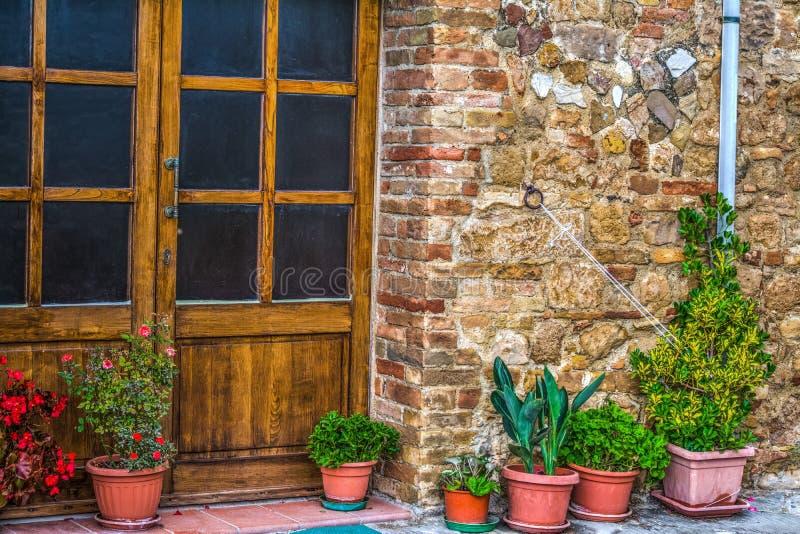 Δοχεία λουλουδιών από μια αγροτική πόρτα στην Τοσκάνη στοκ φωτογραφία
