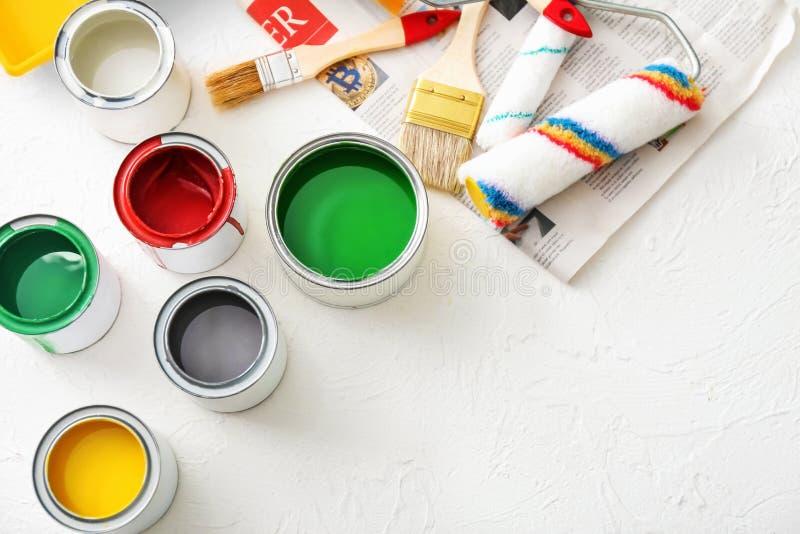 Δοχεία χρωμάτων με τους κυλίνδρους και βούρτσες στο ελαφρύ υπόβαθρο στοκ φωτογραφίες