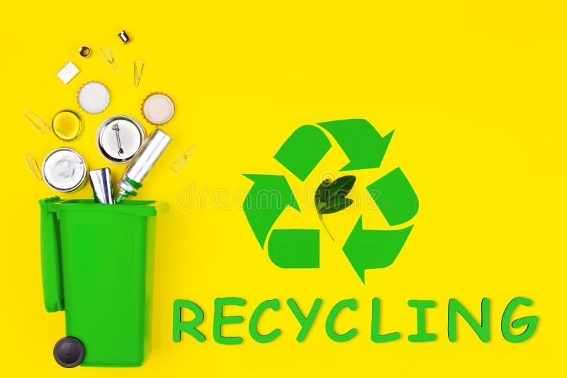 Δοχείο απορριμάτων με τα απορρίμματα μετάλλων για την ανακύκλωση με το πράσινο σημάδι ανακύκλωσης στοκ φωτογραφίες
