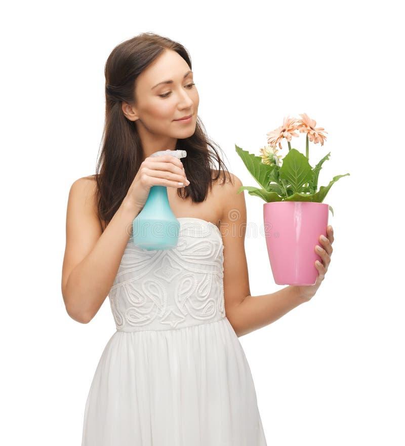Δοχείο εκμετάλλευσης γυναικών με το μπουκάλι λουλουδιών και ψεκασμού στοκ εικόνες