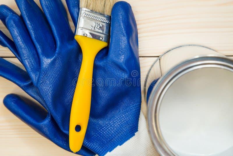 Δοχείο κασσίτερου του οικιακού χρώματος, μιας βούρτσας και ενός ζευγαριού των γαντιών στοκ εικόνα