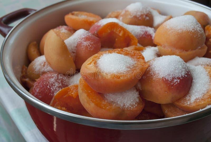 Δοχείο με τα βερίκοκα και ζάχαρη έτοιμη να μαγειρευτεί για να κάνει τη μαρμελάδα στοκ εικόνες