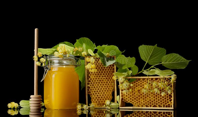 Δοχείο με το μέλι, ξύλινο πλαίσιο με την κηρήθρα που απομονώνεται στο Μαύρο στοκ εικόνα με δικαίωμα ελεύθερης χρήσης