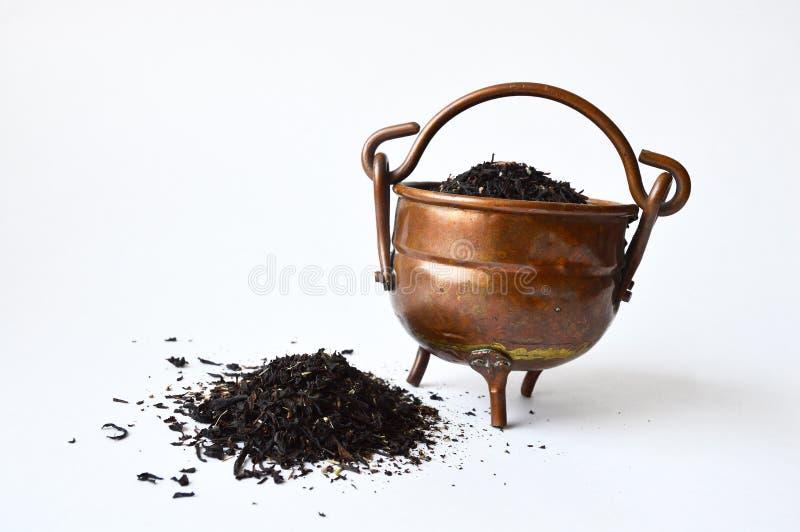 Δοχείο χαλκού του μαύρου τσαγιού με μερικούς που ανατρέπονται έξω στοκ φωτογραφία με δικαίωμα ελεύθερης χρήσης