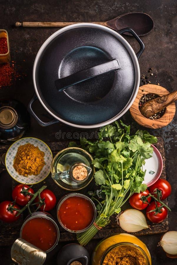 Δοχείο χυτοσιδήρου με τα φρέσκα συστατικά για τη νόστιμη χορτοφάγο σούπα ή τη σάλτσα ντοματών που μαγειρεύει: οι ντομάτες, χορτάρ στοκ φωτογραφίες