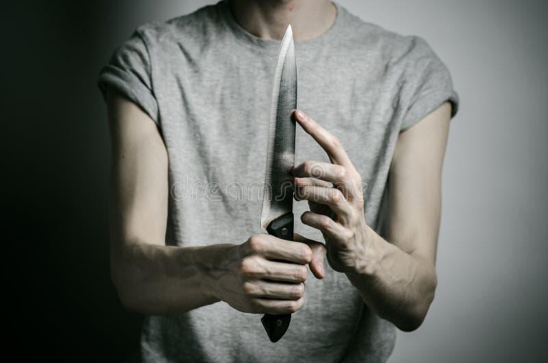 Δολοφονία και θέμα αποκριών: ένα άτομο που κρατά ένα μαχαίρι σε ένα γκρίζο υπόβαθρο στοκ φωτογραφίες με δικαίωμα ελεύθερης χρήσης