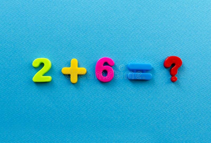 Δράση Math από τους χρωματισμένους πλαστικούς αριθμούς στο μπλε υπόβαθρο εγγράφου στοκ εικόνες
