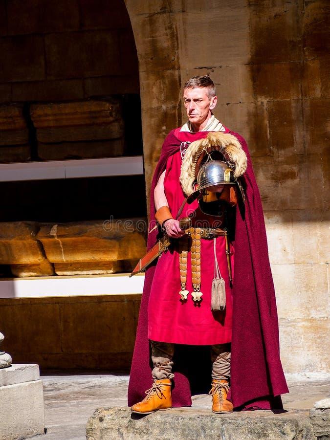 Δράστης στο ρωμαϊκό κοστούμι στρατιωτών στο ρωμαϊκό λουτρό περιοχών ιστορίας, UK στοκ φωτογραφία