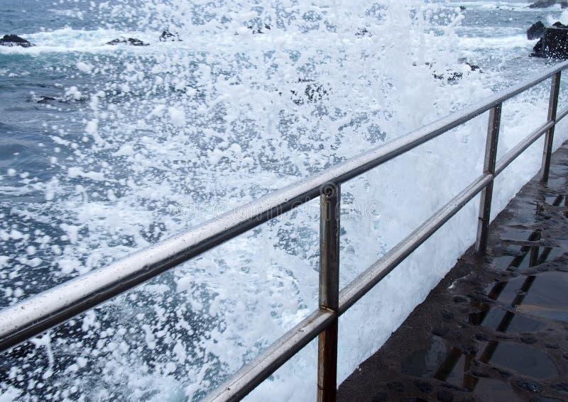 Δραματικά άσπρα υψηλά αφρίζοντας κύματα που συντρίβουν πέρα από τα κιγκλιδώματα χάλυβα σε έναν λιμενοβραχίονα την άκρη μιας θεριν στοκ εικόνες