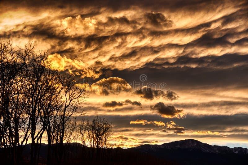 Δραματικά αντιπαραβαλλόμενα σύννεφα στο ηλιοβασίλεμα με τον ουρανό χειμερινής πτώσης βουνών και δέντρων στοκ εικόνα
