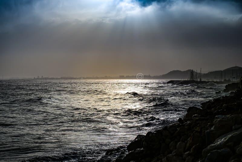 Δραματικές ακτίνες ήλιων μέσω ενός νεφελώδους σκοτεινού ουρανού πέρα από τη θάλασσα στοκ φωτογραφία με δικαίωμα ελεύθερης χρήσης